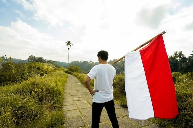 Portret van een man die trots de vlag van indonesië houdt