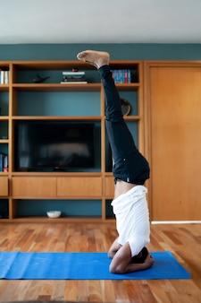 Portret van een man die yogaoefeningen doet terwijl hij thuis blijft. nieuw normaal levensstijlconcept. sportconcept.