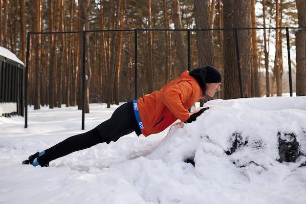 Portret van een man die zich uitstrekt in het park op een mooie besneeuwde winterdag, hardlopen voorbereiden
