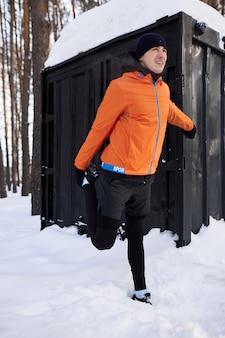 Portret van een man die zich uitstrekt in het park op een mooie besneeuwde winterdag