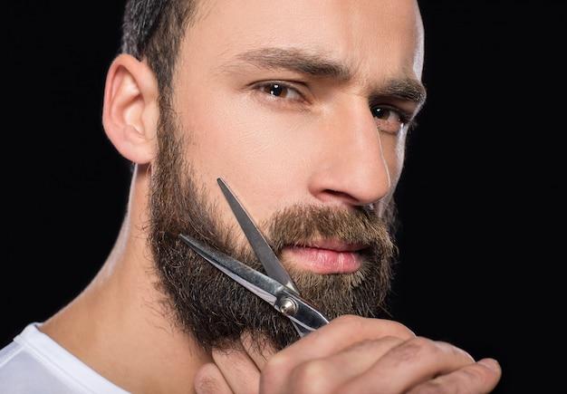 Portret van een man die zijn baard met een schaar snijdt.