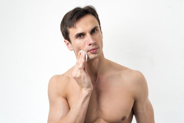 Portret van een man die zijn gezicht schoonmaakt