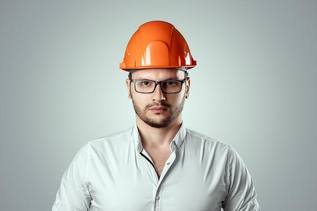 Portret van een man in een bouw oranje helm. conceptenarchitectuur, bouw, techniek, ontwerp, reparatie. ruimte kopiëren