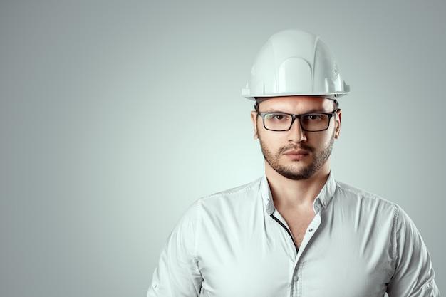 Portret van een man in een constructie witte helm. conceptenarchitectuur, bouw, techniek, ontwerp, reparatie. ruimte kopiëren