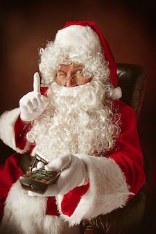 Portret van een man in een kerstman kostuum met een luxe witte baard, kerstmuts en een rood kostuum op rood zittend in een stoel met afstandsbediening van de tv