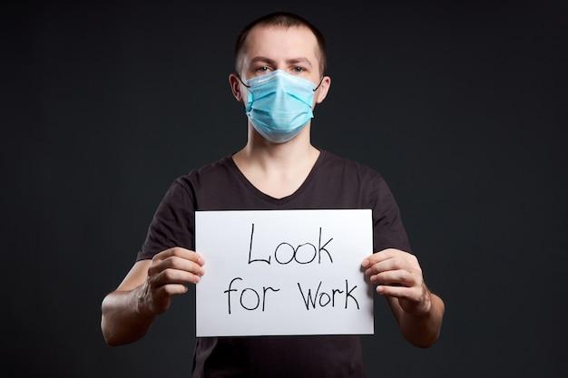 Portret van een man in een medisch masker met een bord op zoek naar werk op een donkere muur, coronavirus infectie