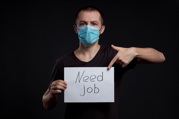 Portret van een man in een medisch masker met een bord voor behoefte aan baan op een donkere achtergrond, coronavirus-infectie