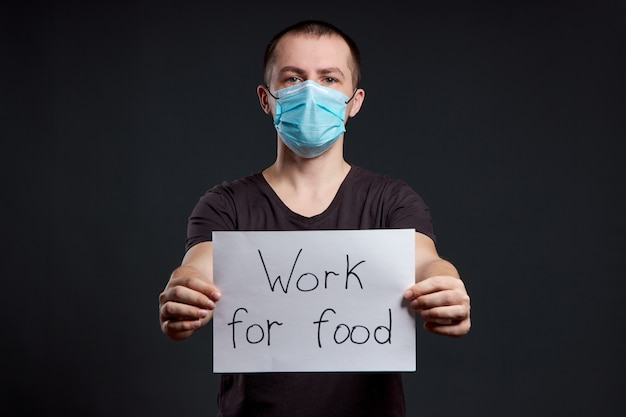 Portret van een man in een medisch masker met een teken werk voor voedsel op een donkere muur, coronavirus infectie