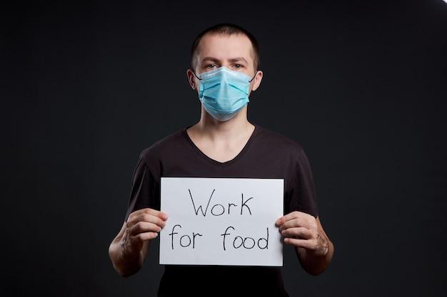 Portret van een man in een medisch masker met een tekenwerk voor voedsel