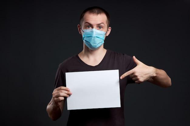 Portret van een man in een medisch masker met wit papier leeg op een donkere muur, coronavirus infectie