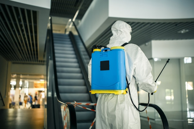 Portret van een man in een ontsmettingspak met spray in de buurt van de roltrap in een leeg winkelcentrum. een vrijwilliger die de openbare plaatsen opruimt om covid-19 te voorkomen. gezondheid bewustzijn concept.