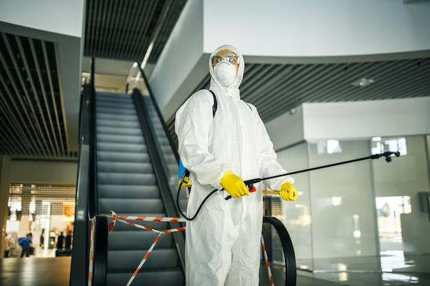 Portret van een man in een ontsmettingspak met spray in de buurt van de roltrap in een leeg winkelcentrum. een vrijwilliger die de openbare plaatsen opruimt om covid-19 te voorkomen. gezondheidsbewustzijn concept.