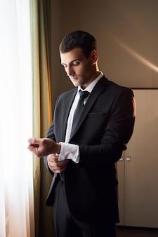 Portret van een man in een pak en stropdas in de buurt van het raam