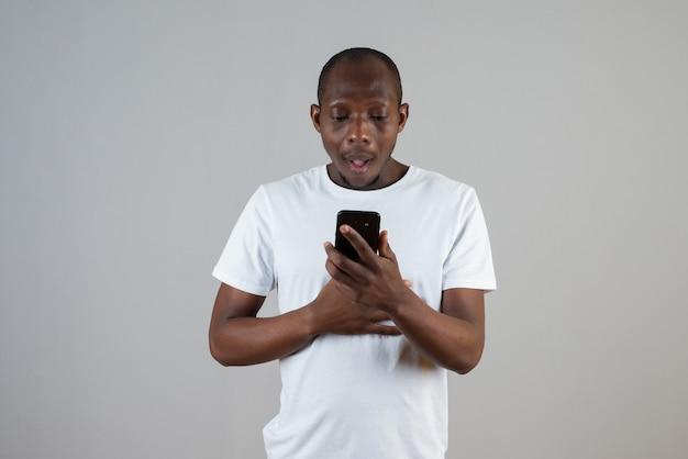Portret van een man in een wit t-shirt die iemand op een grijze muur een bericht stuurt