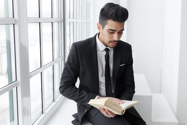 Portret van een man in een zwart pak die koffie drinkt en naar een open boek kijkt. concept onderwijs