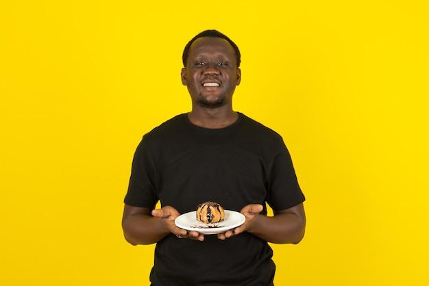 Portret van een man in een zwart t-shirt met een bord cake met chocoladecoating tegen een gele muur