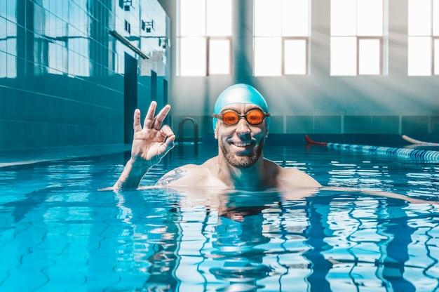 Portret van een man in het zwembad. hij draagt een enorme grappige bril. watersport concept. gemengde media