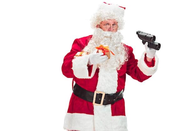 Portret van een man in kerstman kostuum - met een luxe witte baard, kerstmuts en een rood kostuum - in volle lengte geïsoleerd op een witte achtergrond met een verrekijker
