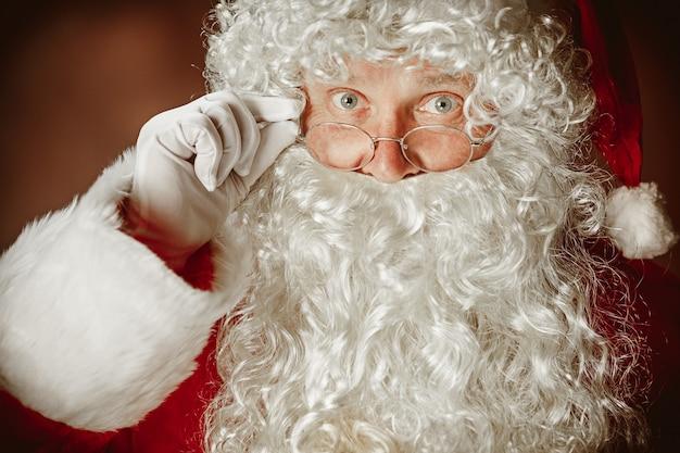 Portret van een man in kerstman-kostuum - met een luxe witte baard, kerstmuts en een rood kostuum op een rode studioachtergrond. het gezicht van dichtbij