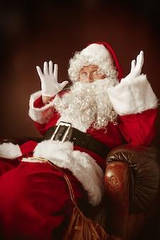 Portret van een man in kerstman-kostuum - met een luxe witte baard, kerstmuts en een rood kostuum op een rode studioachtergrond