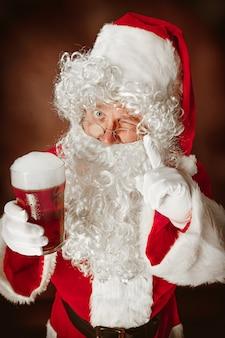 Portret van een man in kerstman kostuum - met een luxe witte baard, kerstmuts en een rood kostuum op rode studio achtergrond met bier