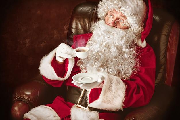 Portret van een man in kerstman kostuum - met een luxe witte baard, kerstmuts en een rood kostuum op rode studio achtergrond zittend in een stoel met een kopje koffie