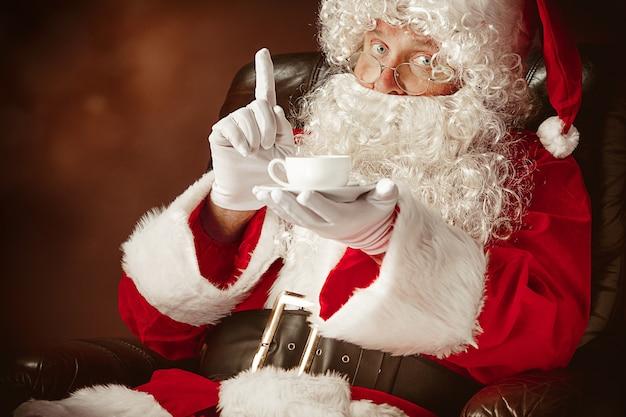 Portret van een man in kerstman kostuum met een luxe witte baard, kerstmuts en een rood kostuum op rood zittend in een stoel met een kopje koffie