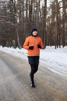 Portret van een man in lichte sportkleding loopt door een winterbos. ijzige dag