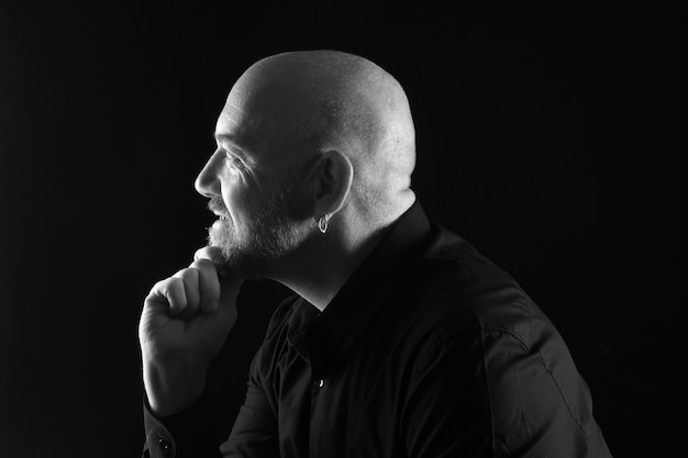 Portret van een man in low key, glimlachend en kijkend naar de kant zwart en wit