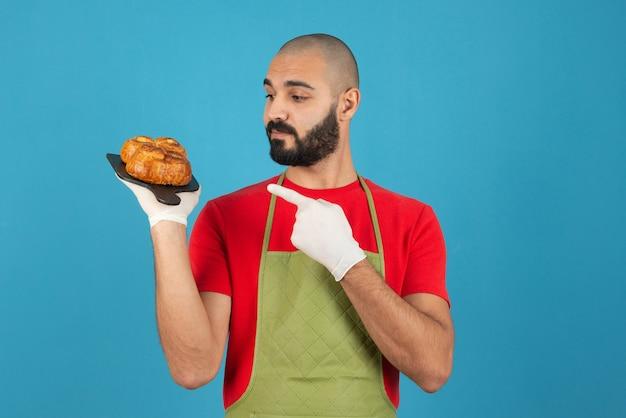 Portret van een man in schort en handschoenen wijzend op een donkere houten plank met vers gebak.