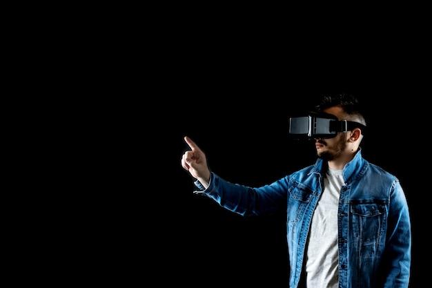 Portret van een man in virtual reality-bril, vr, tegen een donkere achtergrond.