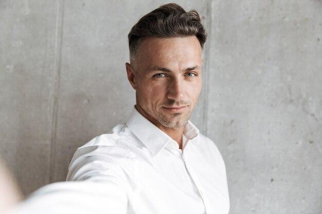 Portret van een man in wit overhemd die een selfie neemt