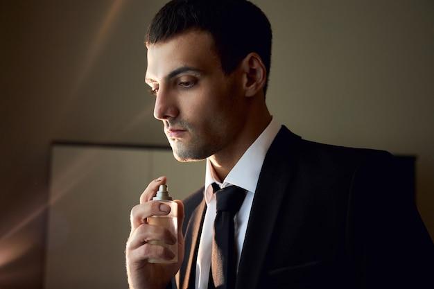 Portret van een man met eau de cologne in zijn handen