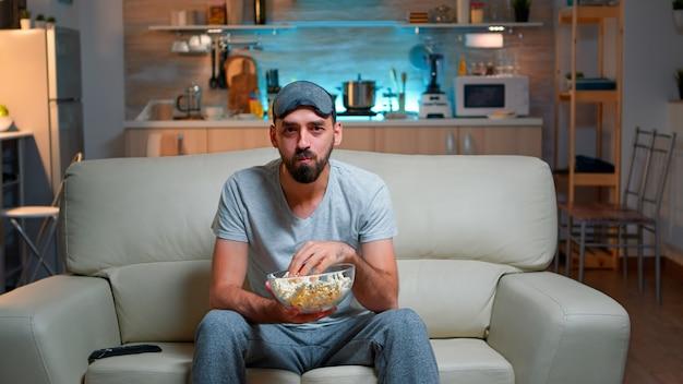 Portret van een man met een baard die een popcornschaal vasthoudt