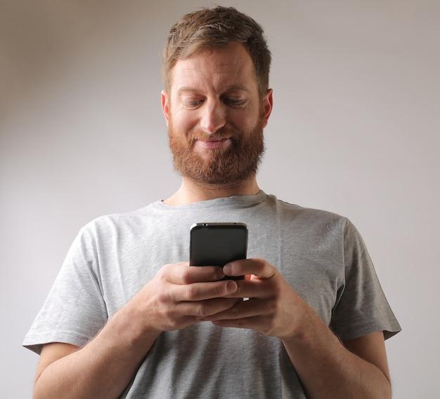 Portret van een man met een baard die enthousiast wordt over een sms