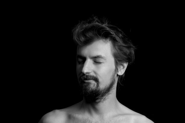 Portret van een man met een baard en warrige haren op een zwarte achtergrond