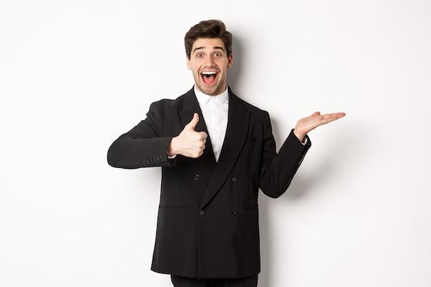 Portret van een man met een baard in een formeel pak, die duim omhoog laat zien en het product in de hand houdt over witte kopieerruimte, product aanbeveelt, staande op een witte achtergrond