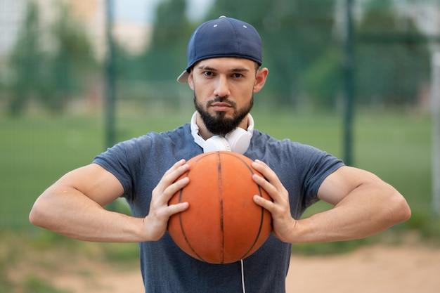 Portret van een man met een basketbal in zijn handen op straat