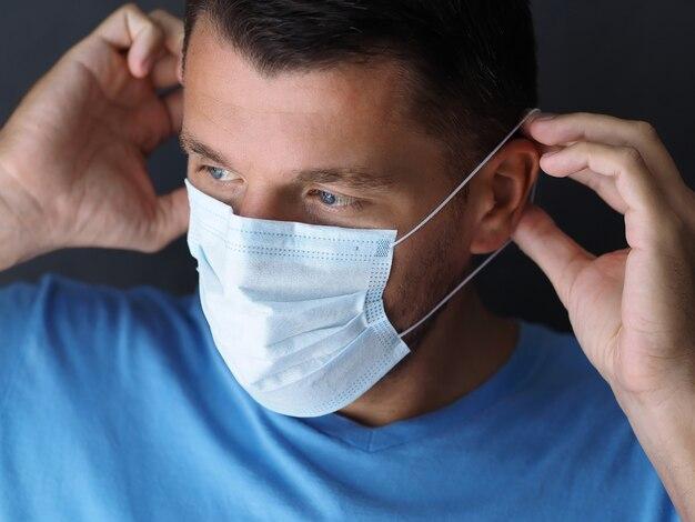 Portret van een man met een chirurgisch medisch masker alvorens het huis te verlaten. covid-19 concept