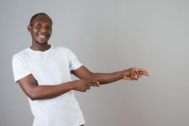 Portret van een man met een donkere huid in een wit t-shirt die iets op een grijze muur wijst