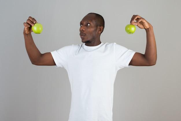 Portret van een man met een donkere huid in een wit t-shirt die naar groene appels op een grijze muur kijkt