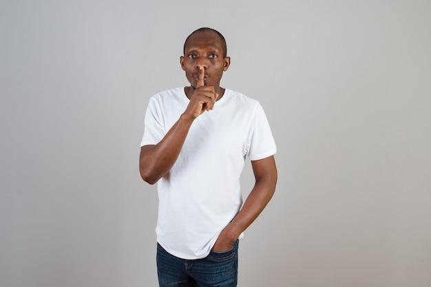 Portret van een man met een donkere huid in een wit t-shirt die staat en zich voordeed op een grijze muur