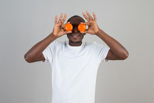 Portret van een man met een donkere huid in een wit t-shirt die zijn ogen verbergt met mandarijnen