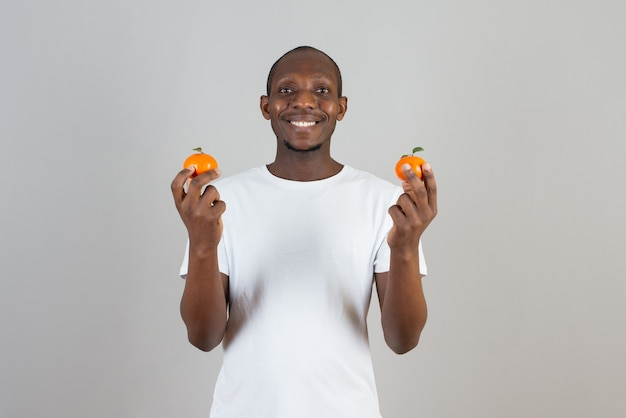 Portret van een man met een donkere huid in een wit t-shirt met mandarijnen op een grijze muur