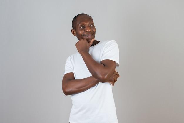 Portret van een man met een donkere huid in een wit t-shirt met staande armen gekruist op een grijze muur