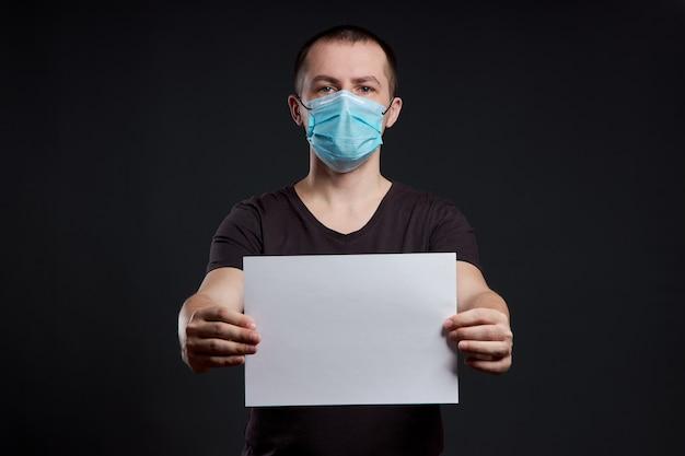 Portret van een man met een medisch masker met wit papier blanco op een donkere achtergrond, coronavirusinfectie Premium Foto