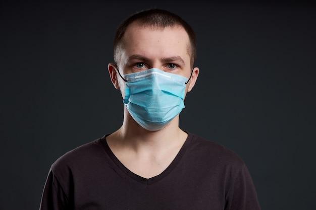Portret van een man met een medisch masker op een donkere achtergrond, een coronavirusinfectie