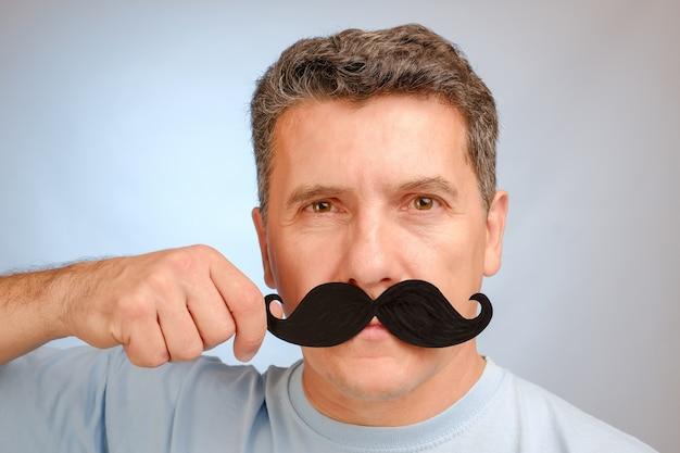 Portret van een man met een nep-snor in de hand om een evenement in november bij te wonen om gezondheidsproblemen bij mannen te bevorderen.