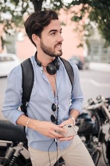 Portret van een man met een smartphone staande voor de motor