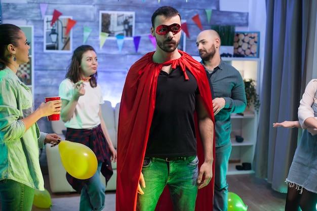 Portret van een man met een superheldenkostuum op een vriendenfeestje.